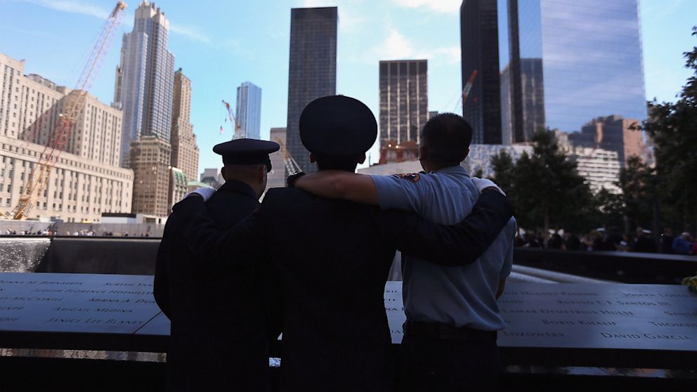 Firefighters embrace at the 9/11 memorial during ceremonies marking the eleventh anniversary of the terrorist attacks on the World Trade Center, Sept. 11, 2012, in New York.