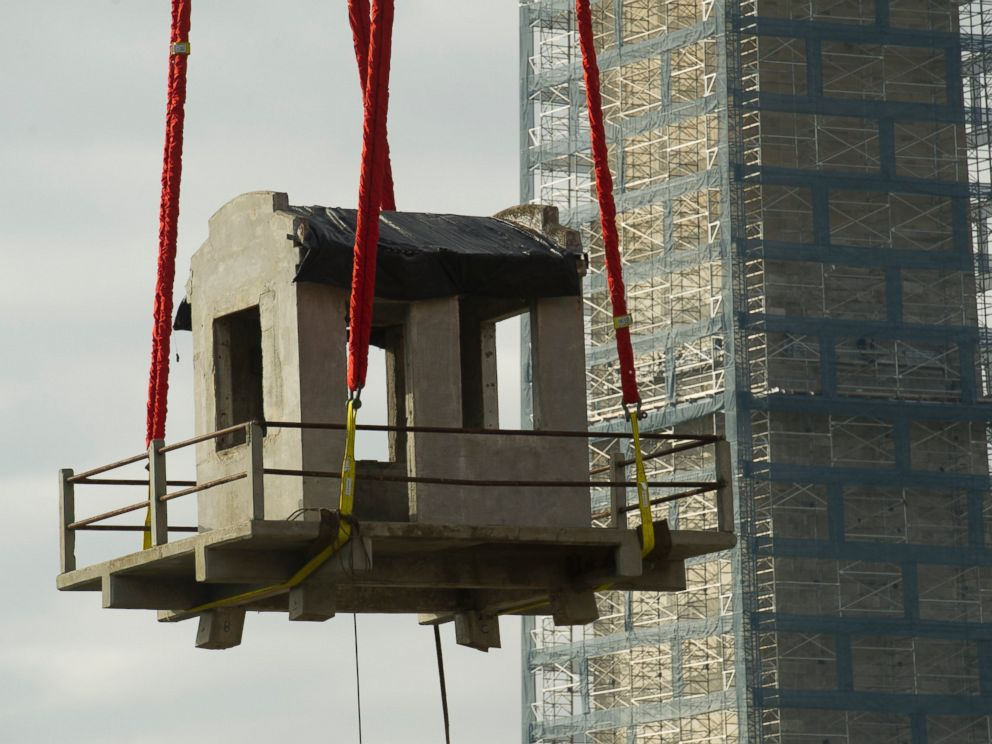 PHOTO: A guard tower from Louisiana State Penitentiary, also known as Angola and The Farm is lowered into the construction site of The National Museum of African American History and Culture in Washington, Nov. 17, 2013.