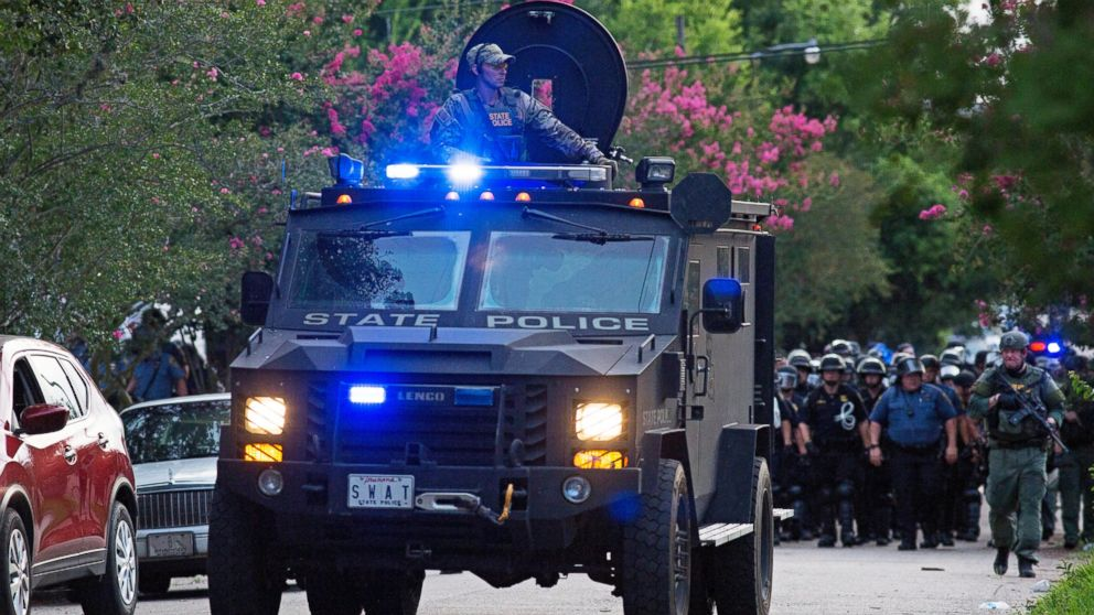 An armored police truck leads a troop of police through a residential neighborhood in Baton Rouge, Louisiana on July 10, 2016. After an organized protest in downtown Baton Rouge protesters wondered into residential neighborhoods and toward a major highway that caused the police to respond by arresting protesters that refused to disperse.