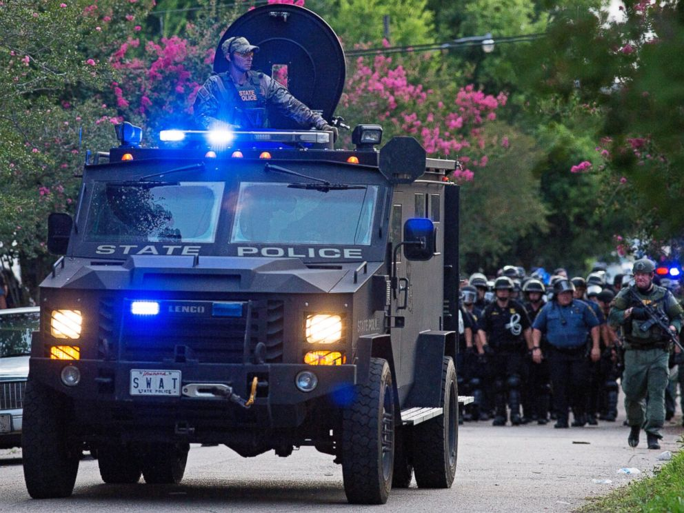 PHOTO: An armored police truck leads a troop of police through a residential neighborhood in Baton Rouge, Louisiana on July 10, 2016.