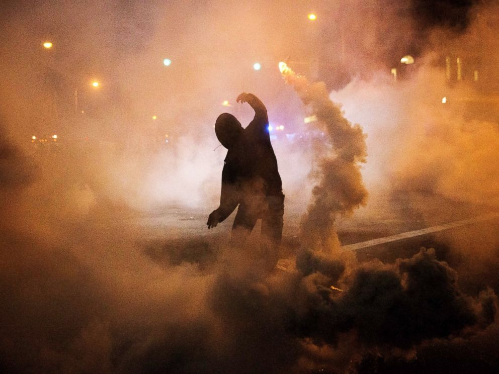 PHOTO: A protester throws a tear gas canister back toward riot police after a 10 p.m. curfew went into effect, April 28, 2015, in Baltimore.