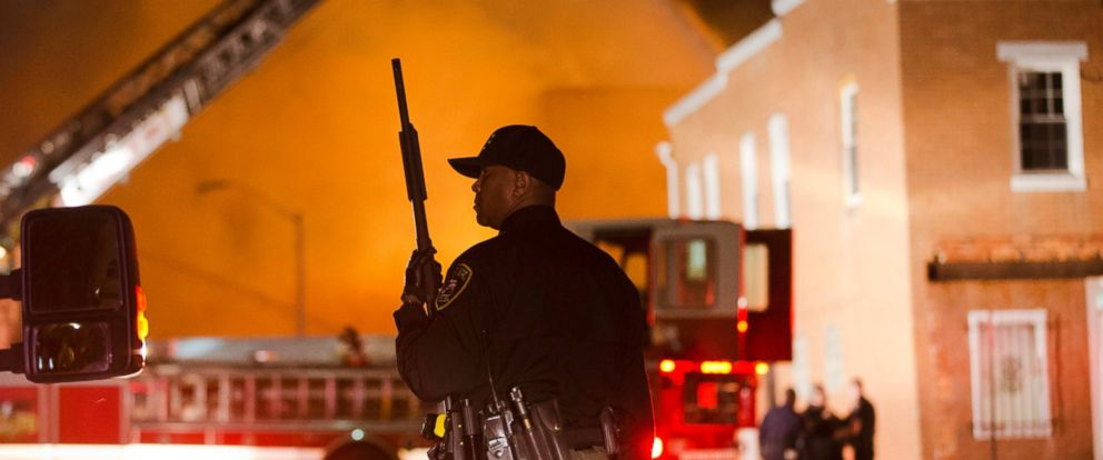 PHOTO: An officer stands near a fire in Baltimore, April 27, 2015, amid violence in the city.