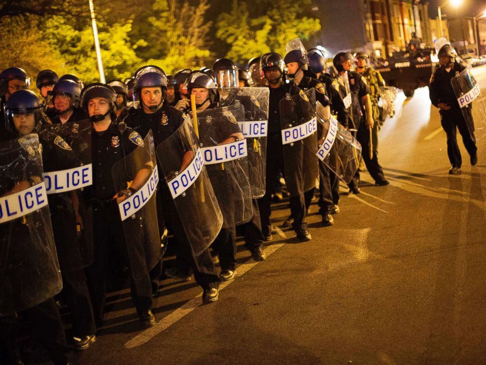 PHOTO: Police in riot gear line up near the scene of Mondays riots ahead of a 10 p.m. curfew, April 29, 2015, in Baltimore.