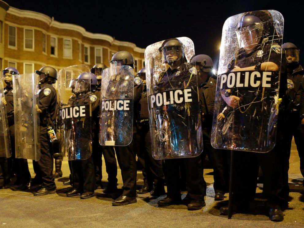 Police stand in formation as a curfew approaches, Tuesday, April 28, 2015, in Baltimore, a day after unrest that occurred following Freddie Grays funeral.