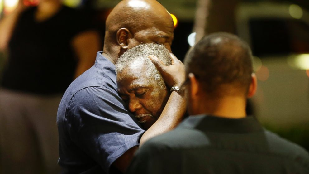 Worshippers embrace following a group prayer across the street from the scene of a shooting at a church in Charleston, South Carolina, June 17, 2015.