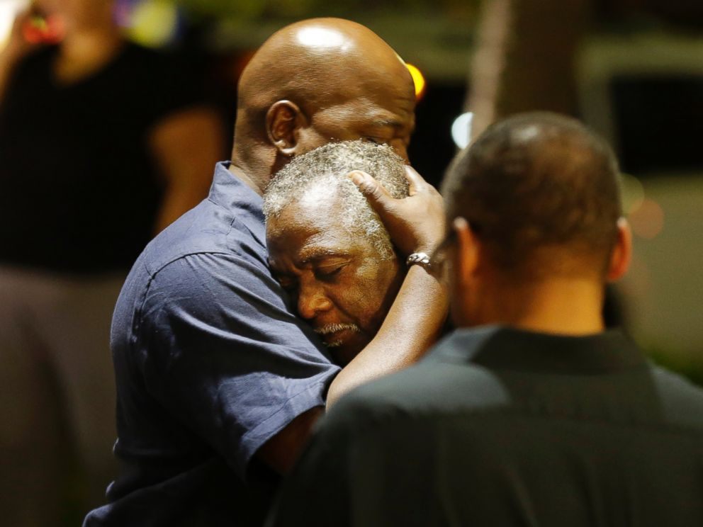 PHOTO: Worshippers embrace following a group prayer across the street from the scene of a shooting at a church in Charleston, South Carolina, June 17, 2015.