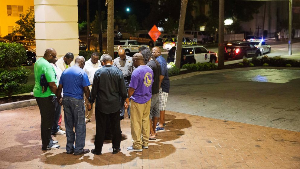 Worshippers gather to pray in a hotel parking lot across the street from the scene of a shooting, June 17, 2015, in Charleston, South Carolina.