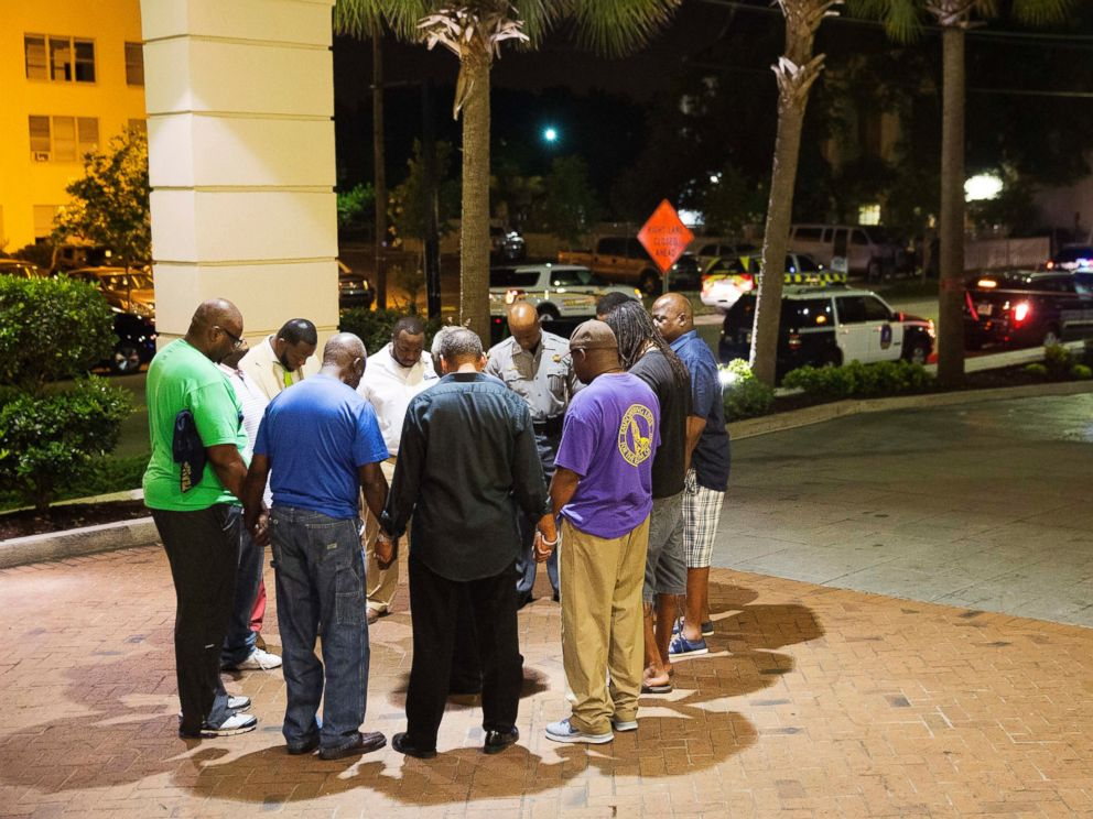 PHOTO: Worshippers gather to pray in a hotel parking lot across the street from the scene of a shooting, June 17, 2015, in Charleston, South Carolina.