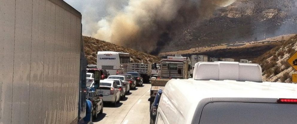PHOTO: Smoke from a wildfire rises above Interstate 15 on the Cajon Pass, Friday, July 17, 2015, near San Bernadino, Calif., as a fast-moving wildfire swept across the Southern California freeway.