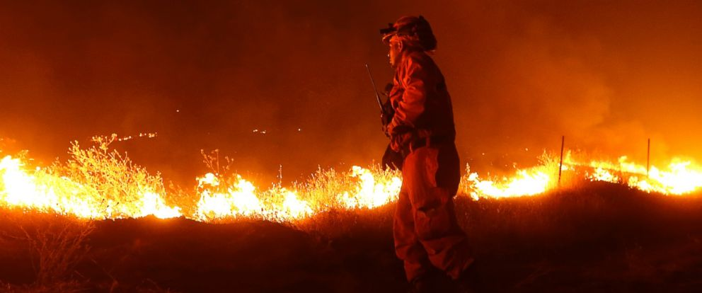 PHOTO: An inmate from the California Department of Corrections and Rehabilitation stands guard as flames from the Butte Fire approach a containment line Saturday, Sept. 12, 2015 near San Andreas, Calif.