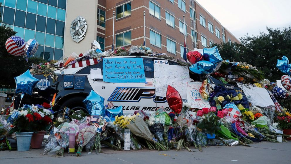 Two Dallas police patrol cars are covered with notes, flowers, balloons and other items as part of a makeshift memorial at the headquarters, July 10, 2016, in Dallas.