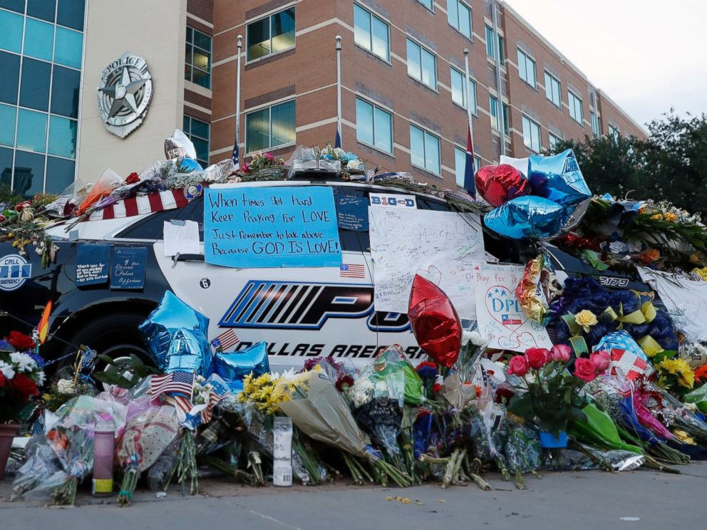 PHOTO: Two Dallas police patrol cars are covered with notes, flowers, balloons and other items as part of a makeshift memorial at the headquarters, July 10, 2016, in Dallas.
