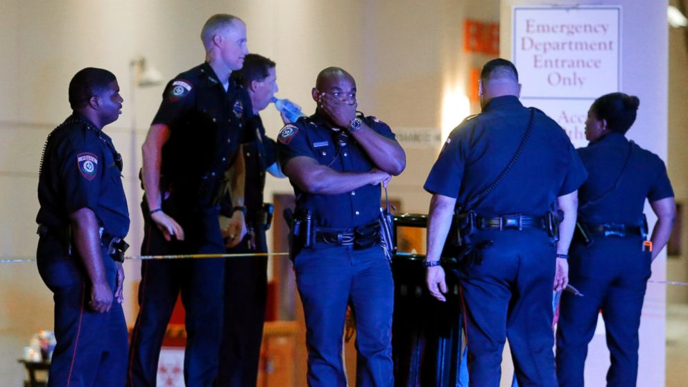A Dallas police officer covers his face as he stands with others outside the emergency room at Baylor University Medical Center, July 8, 2016, in Dallas.