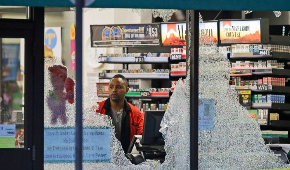 PHOTO: A clerk looks at broken windows shot out at a store in downtown Dallas, July 8, 2016.