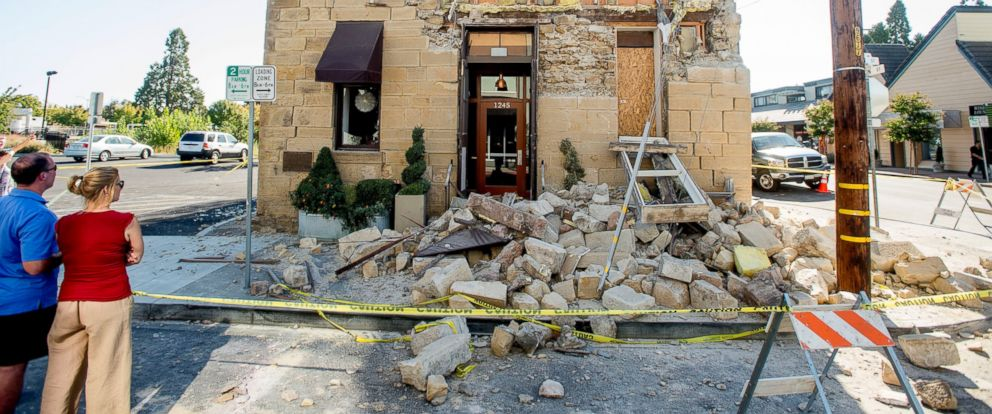 PHOTO: Pedestrians stop to examine a crumbling facade at the Vintners Collective tasting room in Napa, Calif., following an earthquake, Aug. 24, 2014.
