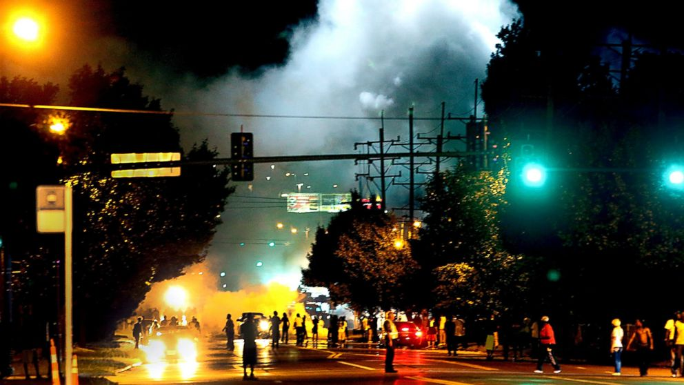 Police officers work their way north on West Florissant Avenue in Ferguson, Mo., clearing the road with the use of tear gas and smoke bombs, Aug. 13, 2014.
