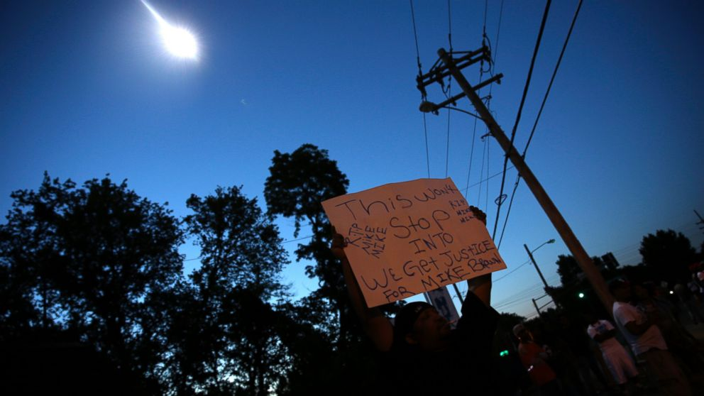 A protester holds up a sign as a police helicopter circles overhead, Aug. 13, 2014, in Ferguson, Mo.