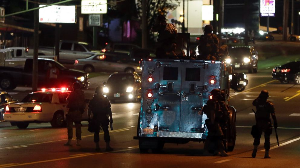 Police attempt to secure a street after a clash with protesters, Aug. 13, 2014, in Ferguson, Mo.