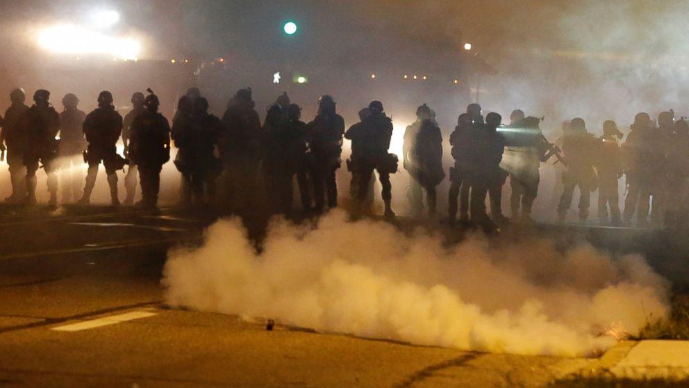 Police advance through smoke, Aug. 13, 2014, in Ferguson, Mo.
