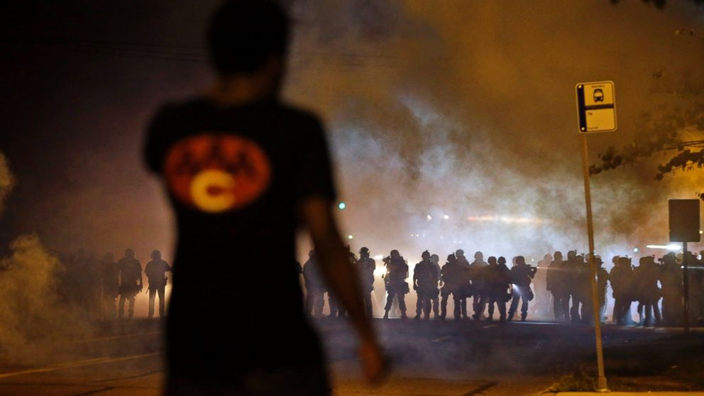 A man watches as police walk through a cloud of smoke during a clash with protesters, Aug. 13, 2014, in Ferguson, Mo.