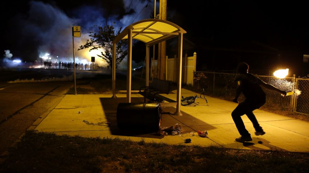 A man picks up a flaming bottle and prepares to throw it as a line of police advance in the distance, Aug. 13, 2014, in Ferguson, Mo.