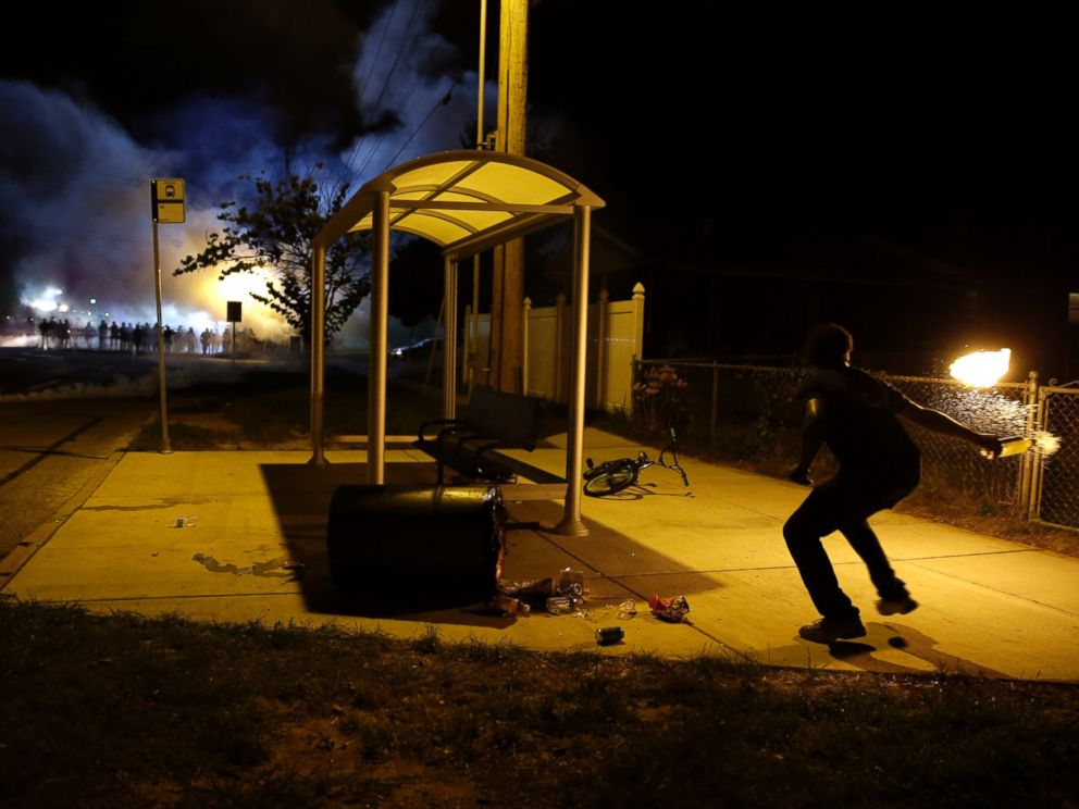 PHOTO: A man picks up a flaming bottle and prepares to throw it as a line of police advance in the distance, Aug. 13, 2014, in Ferguson, Mo.