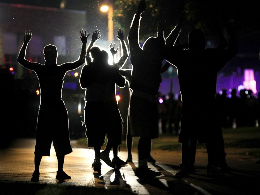 PHOTO: People raise their hands in the middle of the street as police wearing riot gear move toward their position trying to get them to disperse, Aug. 11, 2014, in Ferguson, Mo.