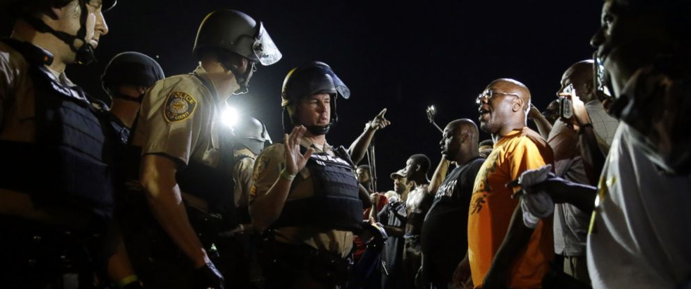 PHOTO: Officers and protesters face off along West Florissant Avenue, Aug. 10, 2015, in Ferguson, Mo.