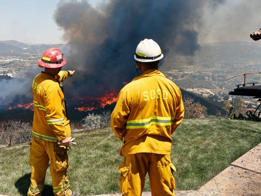PHOTO: Firefighters plan their attack as the brush fire flares up heading toward homes, May 15, 2014, in San Marcos, Calif.