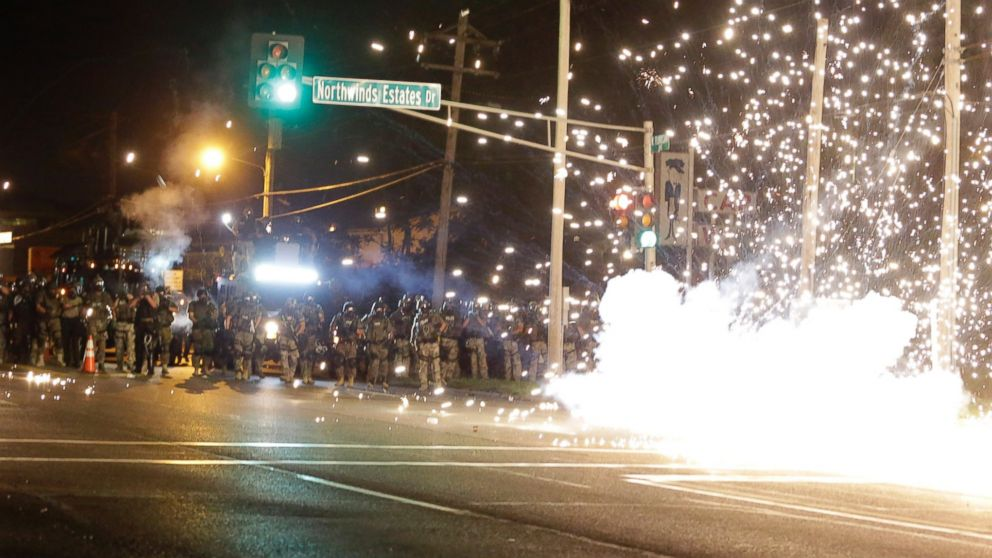 A device deployed by police goes off in the street as police and protesters clash Wednesday, Aug. 13, 2014, in Ferguson, Mo. Authorities in the St. Louis suburb where an unarmed black teen was shot and killed by a police officer have used tear gas to try to disperse protesters after flaming projectiles were thrown from the crowd.