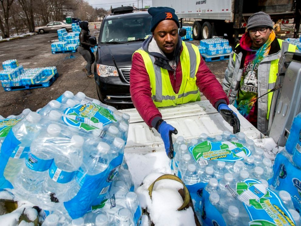 PHOTO: Water distribution employee Albrey Kirkland places water cases into the back of a pickup at a water distribution center on North Franklin Avenue, April 5, 2018 in Flint, Mich.