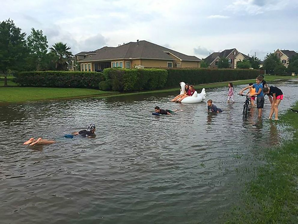 PHOTO: Children play in flood waters in the Kelliwood Park neighborhood of Katy, Texas, April 18, 2016. Flooding in and around Houston has killed at least five people and prompted mass rescues, reports said.