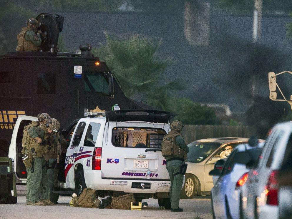PHOTO: Law enforcement officers surround a shooting suspect in his car, July 9, 2014, in Spring, Texas.