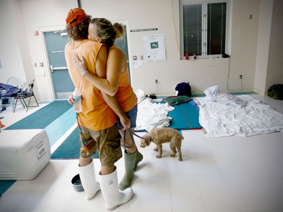 PHOTO: Chris Hacker, left, hugs his girlfriend Lyn Charlton after the couple arrived at an elementary school with their dog, Sept. 2, 2016, in Steinhatchee, Florida.