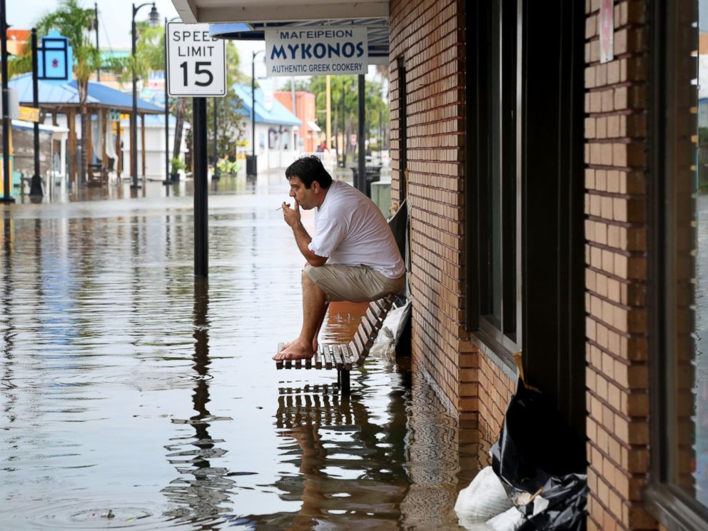 PHOTO: Pedro Muacaj rests on higher ground in front of a gift shop along a flooded section of Dodecanese Blvd. in Tarpon Springs, Fla. where he was working, Sept. 1, 2016.