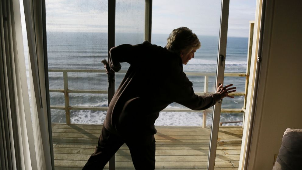 Eileen Horan shuts the door to her patio overlooking the Pacific Ocean after being forced to evacuate her apartment on Jan. 25, 2016, in Pacifica, Calif.