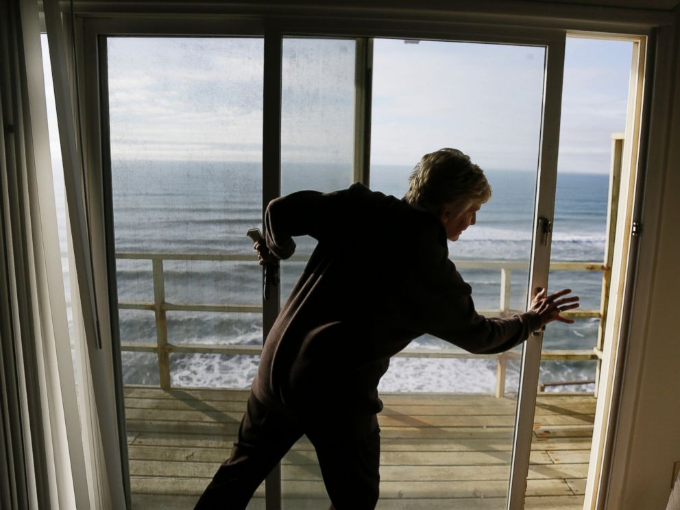 PHOTO: Eileen Horan shuts the door to her patio overlooking the Pacific Ocean after being forced to evacuate her apartment on Jan. 25, 2016, in Pacifica, Calif.