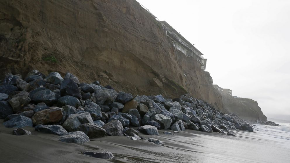 Boulders shore up an eroding cliff below an apartment complex, Jan. 25, 2016, in Pacifica, Calif. Strong waves caused by El Nino storms ate away part of a sea wall and cliffs threatening several homes and an apartment building.