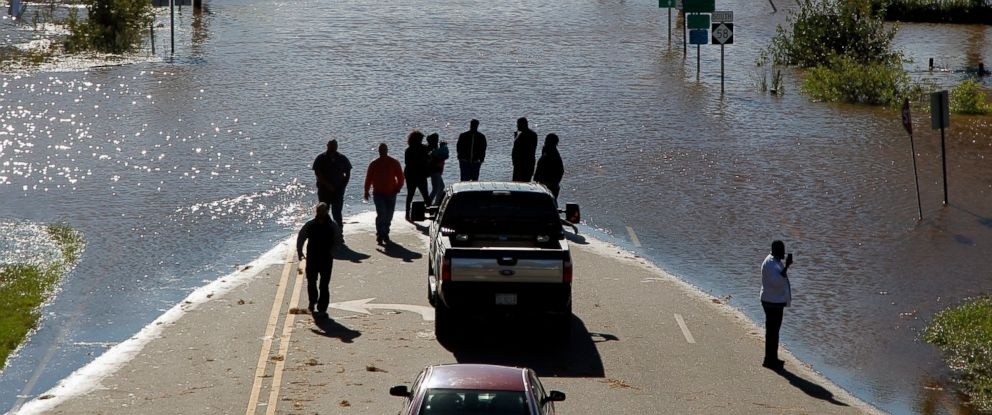 PHOTO: People stop to look and take photos of the floodwaters washing over highway 58 in Nashville, North Carolina, seen from the highway 64 overpass, on ,Oct. 9, 2016.