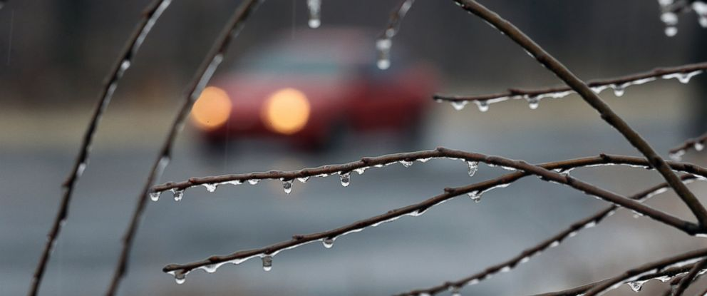 PHOTO: A car drives slowly in the rain on an icy rural road, Jan. 18, 2015, near Newtown, Pa.