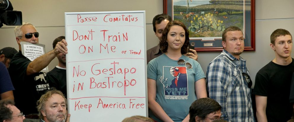 PHOTO: Bob Welch, standing at left, and Jim Dillon, hold a sign at a public hearing about the Jade Helm 15 military training exercise in Bastrop, Texas, April 27, 2015.