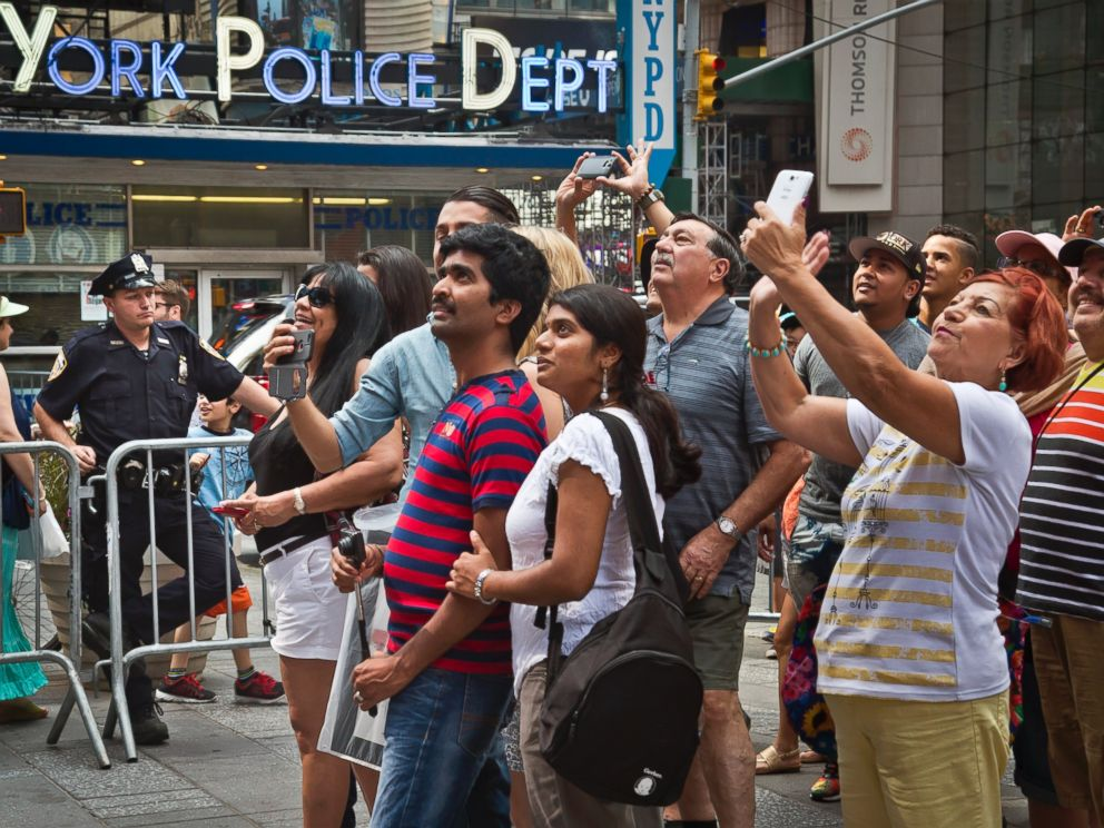 PHOTO: A New York police officer stands watch as visitors stage selfies for a giant monitor playback in Times Square, Friday, July 3, 2015, in New York.