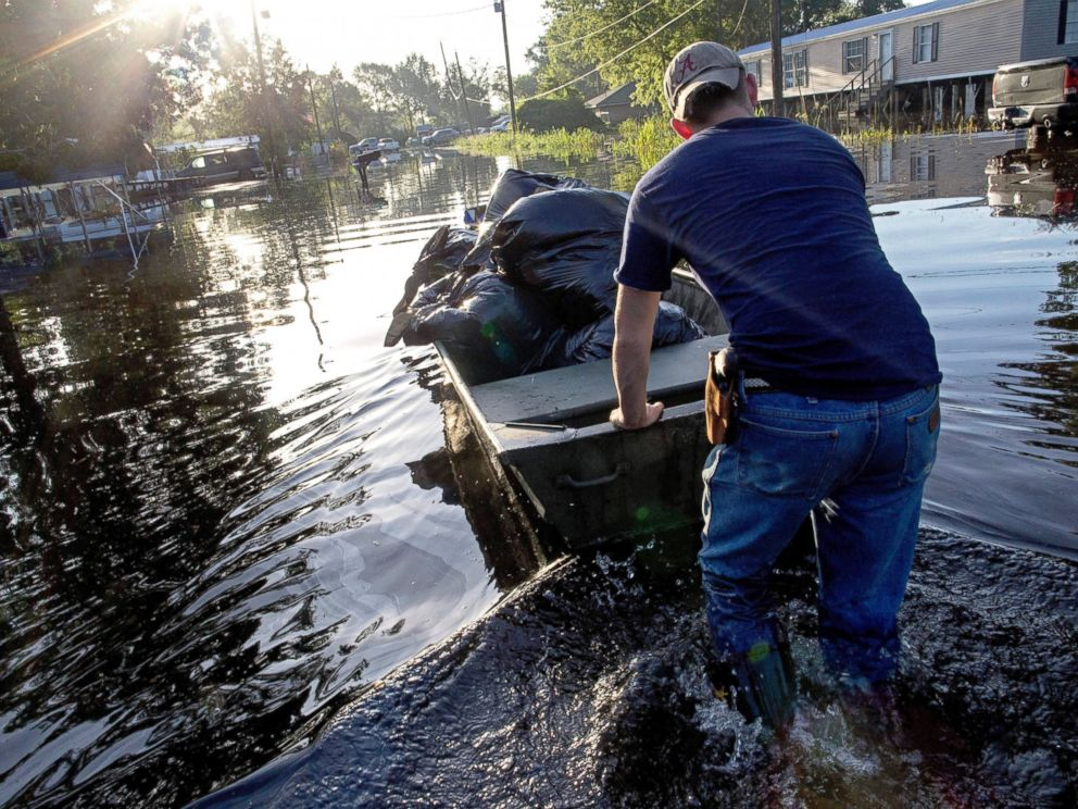 PHOTO: Daniel Stover, 17, moves a boat of personal belongings from a flooded friends home, Aug. 20, 2016, in Sorrento, Louisiana.