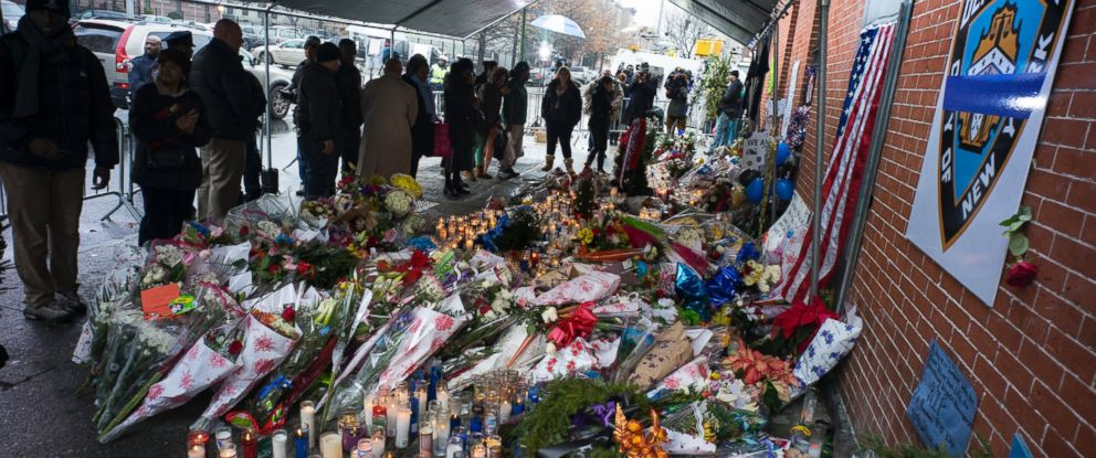 Candles and other items left by visitors make up a growing makeshift memorial, Dec. 23, 2014, near the site where New York Police Department officers Rafael Ramos and Wenjian Liu were slain in the Brooklyn borough of New York.