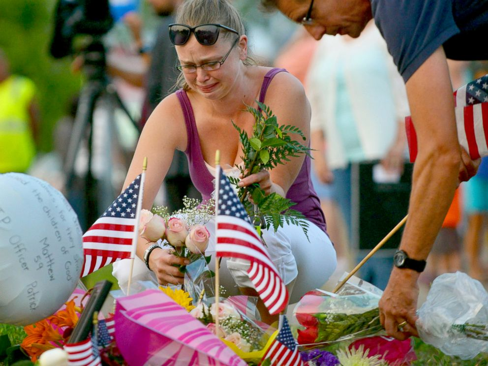 PHOTO: Gail Krull of West St. Paul, Minn. cries as she lays a bouquet of roses on a makeshift memorial following a fatal shooting in West St. Paul, Minn., July 30, 2014.