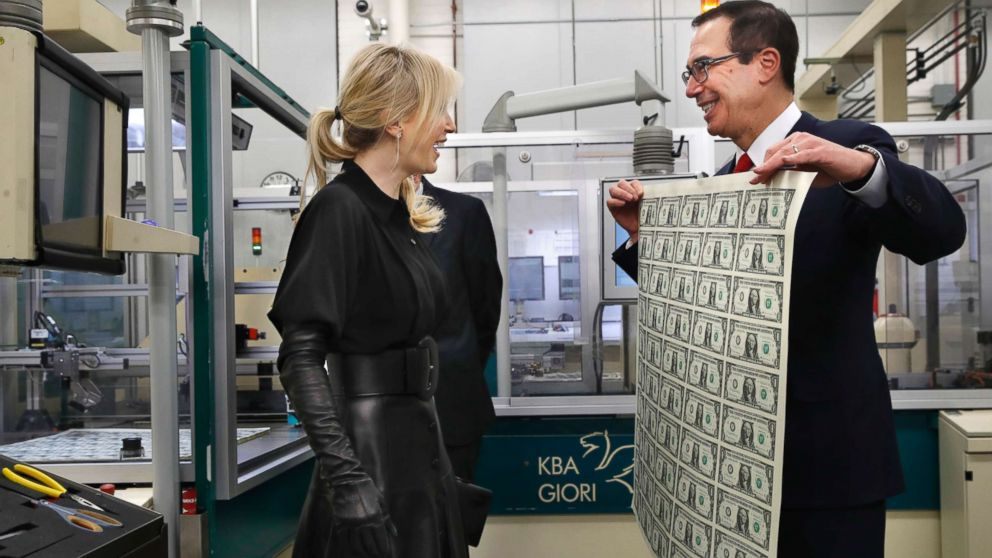 Treasury Secretary Steven Mnuchin, right, and his wife Louise Linton, left, react as Mnuchin holds up a sheet of new $1 bills, the first currency notes bearing his and U.S. Treasurer Jovita Carranza's signatures, Wednesday, Nov. 15, 2017, at the Bureau of Engraving and Printing in Washington.