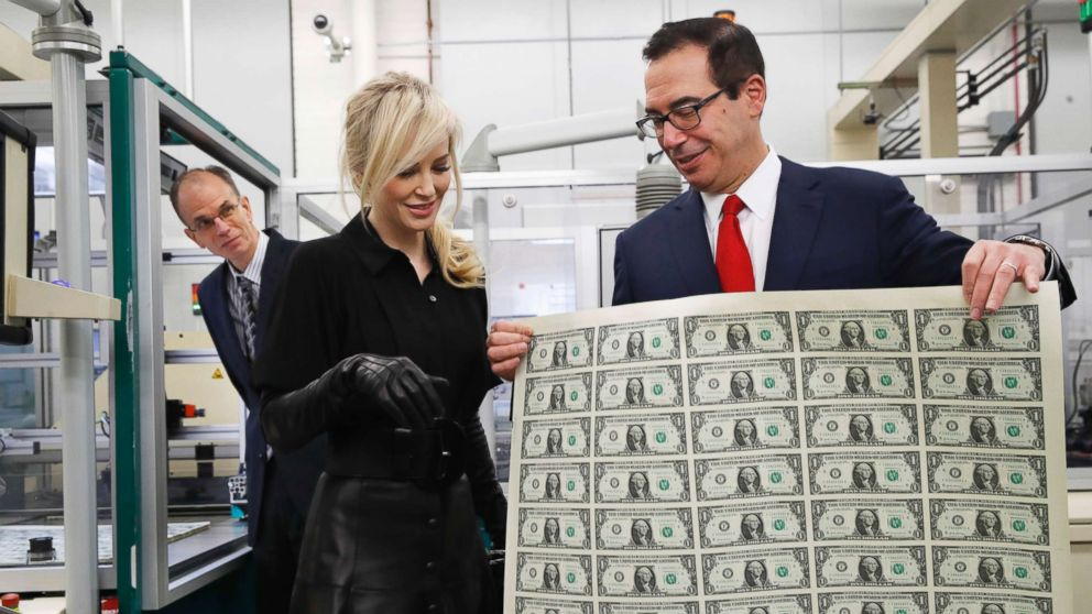 Treasury Secretary Steven Mnuchin, right, shows his wife Louise Linton a sheet of new $1 bills, the first currency notes bearing his and U.S. Treasurer Jovita Carranza's signatures, Wednesday, Nov. 15, 2017, at the Bureau of Engraving and Printing (BEP) in Washington.