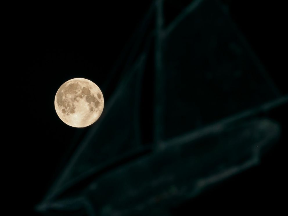 PHOTO: A full moon ascends behind a sailboat-themed weather vane in the city of Oconomowoc, Wis., Sept. 8, 2014.