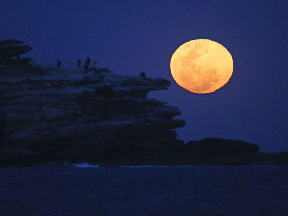 PHOTO: The moon rises with an orange glow as people watch from a rock cliff at Bondi Beach in Sydney, Sept. 9, 2014.