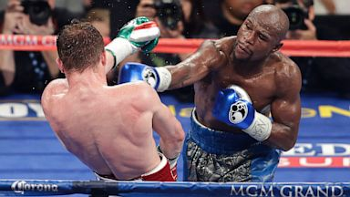 PHOTO: Floyd Mayweather Jr. throws a punch against Canelo Alvarez